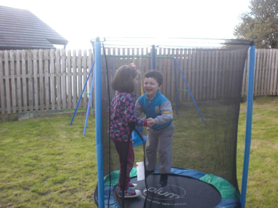 Hailey helping Conor jump on the trampoline.x